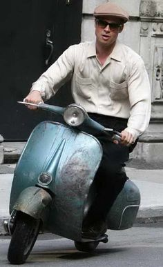 Brad Pitt on a antique scooter.