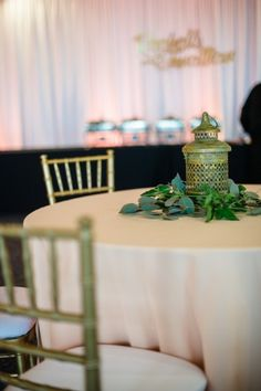 Vintage lantern surrounded by greens- great idea for a unique centerpiece!