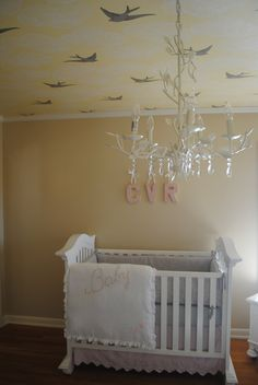 Pale #yellow walls perfectly match the yellow #birds on the #ceiling in this #nursery.