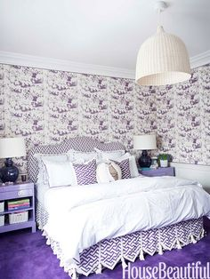 A purple bedroom with China Seas Tableau wallpaper and China Seas Aga fabric for the headboard and dust skirt.
