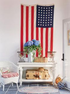 large american flag hangs on the wall with blue flowers on a white table in front