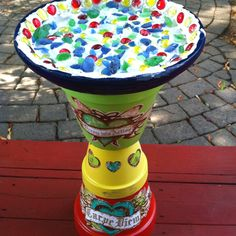 I made this bird bath out of 3 Clay pots . The top is the watering base of one large pot . They were painted , then a weatherproof overlay . The decals on the front are wall adhesives , but you could  stencil as well. Plaster of Paris for the bottom and then glass rocks and marbles . It's important to use a strong washable silicone glue as adhesive to glue the pots . It was about 25.00 to make and took 3 days to complete .