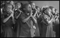Children in a small school in Jamaica praying