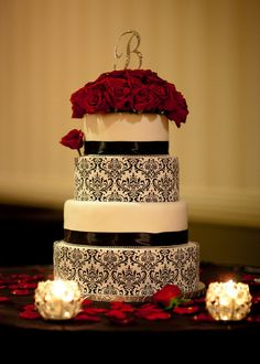 Black & White Wedding cake:  Round Tiers with black scroll work, black ribbon and red Roses