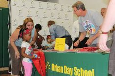 """Bucks GM John Hammond and members of the Bucks staff, and mascot Air Bango, teamed up with Sam's Hope in partnership with First Book at Urban Day School for the Summer """"Snuggle Up and Read"""" event."""