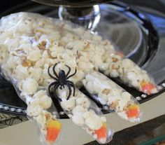 """Purchase food-safe non-latex gloves and place one candy corn inside the tips of each finger (to create the """"fingernails"""") and fill the rest with popcorn. Secure with a black string around the wrist."""