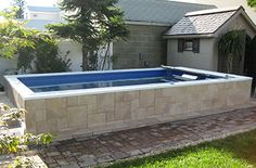 Partially above ground Endless Pool with stone and tile.