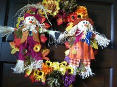 Decorative Colorful Autumn Wreath with Boy and Girl Scarecrows.  Full of fall colors 14 inch wreath This colorful autumn seasonal wreath features orange, red, yellow, mauve leaves and flowers arranged on a straw wreath. Fall wreath is perfect for any wall or autumn display in any home. Wreath is made from straw and we added the two different cute scarecrows dressed in burlap and fall colors. Boy and girl scarecrows holding hands. https://www.etsy.com/shop/CountryCraftsnflower