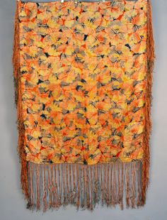 ART DECO PRINTED and METALLIC BROCADE SILK SHAWL, 1920's. Orange, black and goldenrod abstract pattern with a large scale gold brocade floral. 35 x 44 with 14 inch tricolor silk fringe.