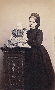 Scottish Mourner, Albumen Carte de Visite, Circa 1870. The mother wears entirely black, including black earrings and a black brooch, while her child wears black shoulder ribbons and a black sash over a black and white dress.
