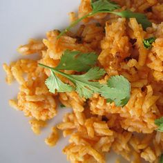 Spanish Rice 1 tablespoon olive oil 1 medium white onion, chopped 3 cloves garlic, minced 1 cup rice 1/2 cup tomato sauce (cantadito) 2 1/2 cups chicken or vegetable broth Salt and freshly ground black pepper Cilantro sprigs, optional for garnish