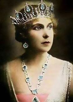 Queen Ena is wearing her Brazilian aquamarine parure, consisting of a tiara, necklace and pendant, two sets of earrings, bracelet, and a two-piece pendant brooch.  The tiara is in its original form before it was remodeled to a series of  interlocking rings in the Vladmir style.
