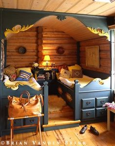 carved twin beds in coastal Maine island log home; connected–platform flows into beds' footboards, side rails merge into shared nightstand, corner posts climb walls to hold gently curved canopy; Norwegian carpenters carved waves of blue-green painted wood crested with yellow foam flourishes.