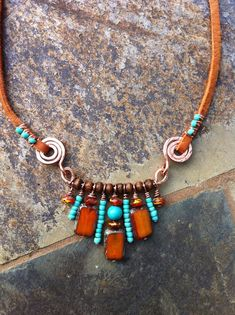 necklace: wire wrapping the beads around the leather cords; spacing the pattern with the small wooden beads between them