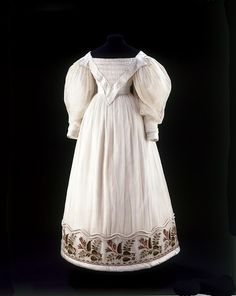 Dress  Place of origin:  Great Britain (possibly, made)   France (possibly, made)    Date:  ca. 1830 (made)    Artist/Maker:  Unknown (production)    Materials and Techniques:  Cotton muslin with wool embroidery, silk satin and wadded rouleaux
