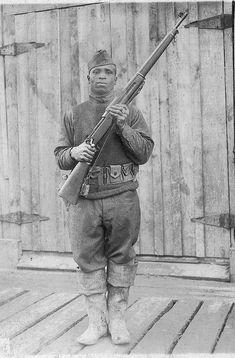Black American World War I soldier holding a U.S. model Enfield rifle (c. 1917) .