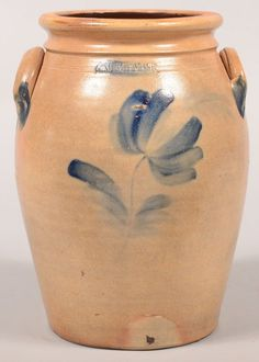 """Sold $ 325 Wm. Moyer (Harrisburg, PA) Tulip Decorated 1 Gallon Stoneware Jar. Circa. 1858-1860. Blue slip single tulip and foliate decoration. Bulbous form with molded rim and applied ear handles. 10 1/2"""" high. Condition: Good with some minor scattered pit marks on back."""