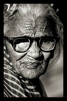 the firm line of character, woman, female, wrinckles, oldie, old lady, glasses, a face that have lived with stories to tell, portrait, photograph, photo b/w.