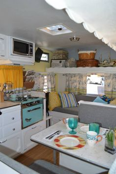 Vintage Camper - beautiful interior--I like the white cabinets and the toile/plaid combination for the window treatments....
