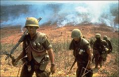 US soldiers on the ground in Vietnam in 1968. The nearer soldier carries an M-60 machine gun. Photo by Larry Burrows