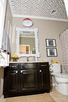 Bathroom: Painted cabinets Black, stenciled Ceiling, new framed mirror- could you frame out existing mirror? -replace hardware