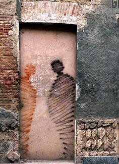 Shadow figures in a concrete doorway
