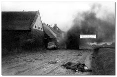 A dramatic picture of battle in a suburb of the German city of Bautzen. A German car Kubelvagen (Kubelwagen) came under fire on the village street. One passenger jumped out the car, but was shot in the street.  The car then turned and ran across the street to the building. The remaining passenger was also killed - (can be seen lying on the right of the car).  In the middle of the road is some big vehicle - a truck or a tank.