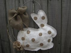 Burlap Door Hanger Easter Bunny- Made of natural burlap with polka dots and burlap tail.The base is painted white and the polka dots are the natural burlap. Adorned with burlap hand tied bow and accented with raffia and hangs on a metal wire. So cute. Can be used all year long. Measures approx 23 inches tall and 19 inches wide. Inspiration.
