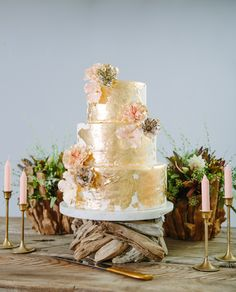 gold wedding cake with flowers, photo by Jenna Saint Martin http://ruffledblog.com/driftwood-wedding-inspiration #weddingcake #cakes
