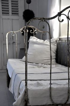 ...the old French shutters and distressed iron daybed look great with the crisp white linens