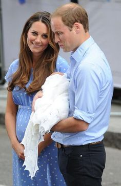Prince William holding his son,  the Prince,  with a glowing Kate looking on.   Meet the world,  young royal!