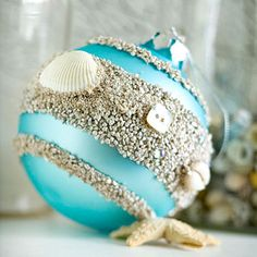 Bring the beach into your Christmas decorating by painting stripes of glue on an aqua-color ornament and sprinkling it with sand. Add small shells and beige buttons for a casual, sunny look.