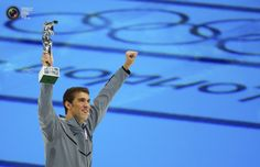 Michael Phelps of the U.S. holds up his award recognising him as the most decorated Olympian