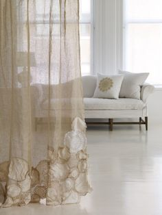 Doilies sewn to sheer curtains.