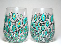 These wine glasses contain a beautiful peacock feather design meticulously painted in black, teal & shimmery gold. MEMBER - Pretty My Drink