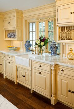 Beautiful farmhouse style kitchen with painted cabinetry and rich wood floors.