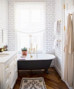 black tub, white subway tile, brass fixtures & hardware