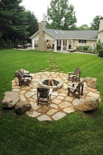 DIY fire pit with surrounding flagstones dug in to be flush with the ground. Now imagine it surrounded by some raised beds.