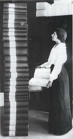Elin Wägner stands next to a tower of books containing the signatures collected in support for women's suffrage in Sweden, 1914. (Photo: Kvinnohistoriska Samlingarna, Göteborg)