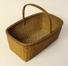 """A superior example of the art of Shaker basket weaving.  Ash and maple retaining an old or original taupe wash.  Essentially the basket equivalent of a Shaker carrier.  New Lebanon, New York.  Circa 1850.  Height to rim, 6 1/2"""", height to top of handle, 11"""", length, 14 1/2"""", width, 9 3/8""""."""