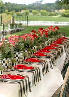 Garden party ~ Mackenzie Childs. She used tin cans and covered them for the flowers. Big check black and white gingham table runners going a...