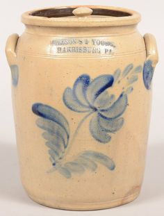 "Sold $ 3,250 Wilson's & Young, Harrisburg, PA Tulip Decorated 1 1/2 Gallon Stoneware Crock. Circa. 1855. Large cobalt blue single tulip and leaf slip design. Ovoid body, molded rim (with lid) and ear handles. Hard to find one year stamp. 10"" high. Condition: Good with a few rim chips."