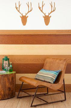Ter uma cabeça de animal em casa não pega muito bem, mas e se ela for feita de adesivo? É bem fácil de fazer: risque a silhueta do animal no verso do adesivo com estampa de madeira, recorte e cole na parede. Na parte inferior da parede, foram coladas tiras de adesivo plástico imitando réguas de madeira de cores diferentes – tudo para dar um ar de aconchego a sala. A cadeira e mesa de tronco são da Raízes Design, a almofada é da Missoni Home.