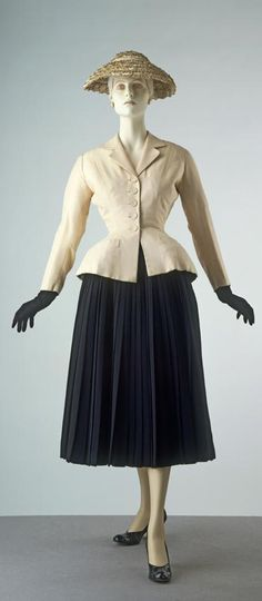 """""""Bar"""" suit and hat (silk shantung jacket, wool crepe skirt, and straw hat) by Christian Dior, French, spring/summer 1947. 'Bar' is one of the most important designs from Dior's first collection. The tight-fitting jacket has padded hips which emphasise the tiny waist. The long pleated wool skirt, backed with cambric, is exceptionally heavy. """"Bar"""" cost 59,000 francs and ushered in the post-war """"New Look""""."""