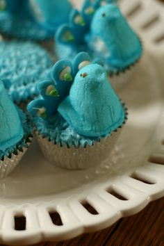 """Peeps peacock cupcake with """"recipe"""": box cake mix + spray can frosting + tail-less peeps + candy bark melted and piped onto wax paper in feather design= pretty!"""