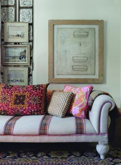 Eclectic Decor - Patterned throw pillows atop a couch with plaid stripes in front of a gallery wall