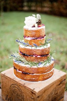 Naked wedidng cake dressed with flowers and herbs
