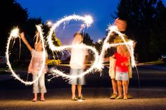Tip #11: Get creative with sparklers.  I made this picture below last year at a family Fourth of July party.  To do a picture like this, (1) Set the camera on a tripod, (2) Choose f/8, ISO100, and set the shutter speed to 15 seconds (15″).  Then press the shutter button and have the people move their sparklers in the shape of whatever word you want to spell.  If they don't move their heads, they won't be blurry, but it was tough to get the kids to be still.  Fun!