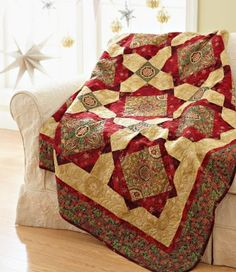Fussy-cut a beautiful fabric to star in the center of gemlike quilt blocks. Choose a holiday print with metallic touches for a throw that really shines.