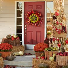 Stuff the bottoms of vintage harvest baskets with newspaper and fill them with fresh apples. Attach dried cornstalks to porch posts with wire hidden under burlap, then use Indian corn, gourds, and vintage rakes and pitchforks to add to the harvest theme. Pots of red mums and red fall leaves, straw bales add layered height.